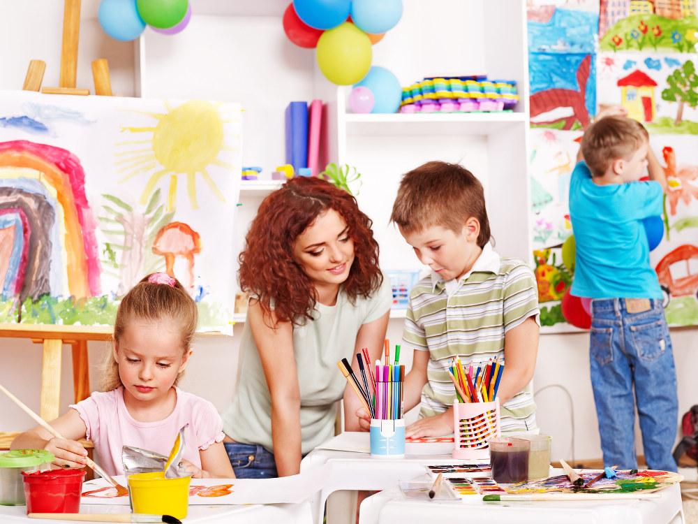 Eine Erzieherin malt mit zwei Kindern