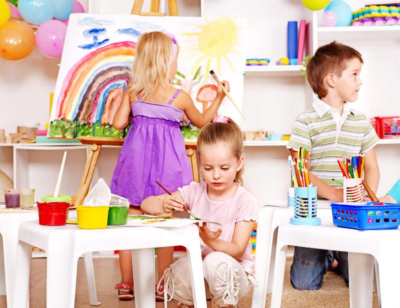 Eine Gruppe von Kinder malt an einer Staffelei